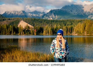 Young hiker in colorful fantastic mountain landscape at gold autumn sunset near Strbske Pleso lake in High Tatras