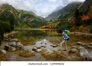 Young hiker in colorful fantastic mountain landscape at gold autumn near Popradske Pleso lake in High Tatras