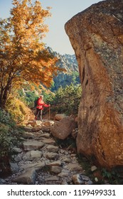Young hiker in colorful fantastic mountain landscape at gold autumn in High Tatras
