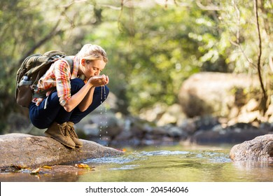young hiker drinking stream water in mountain