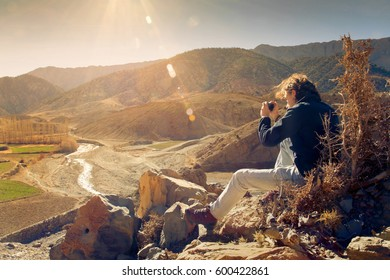 Young hiker enjoying sunset and taking picture on peak of arid mountain in Morocco valley