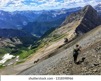 A young hiker exploring the Rocky Mountains on a backcountry hike along the spectacular Northover Ridge trail in Kananaskis, Alberta, Canada.  A beautiful valley is far below.