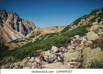 Young hiker in fantastic mountain landscape in spring season near waterfall in High tatras