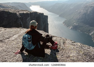 Young hiker girl with backpack sits on the rock's cliff in front of breathtaking panorama of Lysefjord in Kjerag, Norway