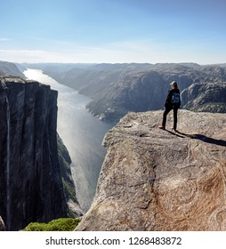 Young hiker girl with a backpack stands on the rock's cliff and observes the breathtaking panorama of Lysefjord in Kjerag, Norway