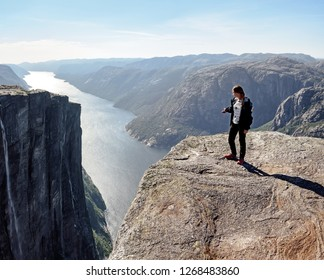 Young hiker girl stands on the rock's cliff and points to the breathtaking panorama of Lysefjord in Kjerag, Norway