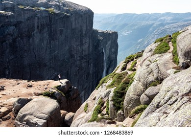 Young hiker girl stands on the rock's edge and observes the breathtaking panorama of Lysefjord in Kjerag, Norway