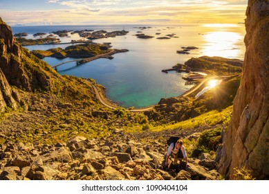 Young hiker going to the top of mount Festvagtinden with views over the village of Henningsvaer on Lofoten islands in Norway
