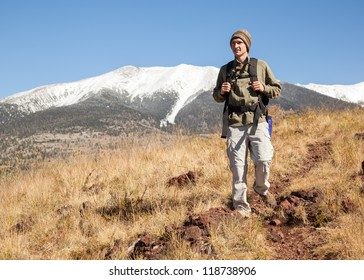 Young hiker on mountain footpath with snow-capped mountain in background. (Humphrey's Peak in Flagstaff, Arizona)