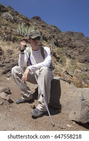 young hiker sitting on the rock in strong sun, resting