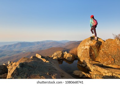 A young hiker standing on the top of Stony Man Summit at Shenandoah National Park at sunset, Virginia, USA. Shenandoah National Park extends along the Blue Ridge Mountains in Virginia USA.