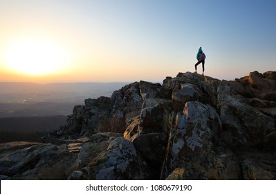 A young hiker standing on the top of Stony Man Summit at sunset at Shenandoah National Park, Virginia, USA. Shenandoah National Park extends along the Blue Ridge Mountains in Virginia USA.