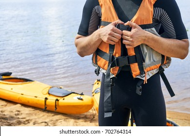 Young hiker wearing wetsuit putting on a life jacket before sailing on kayak