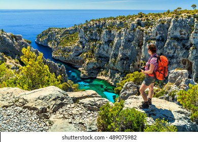 Young hiker woman with backpack and photo camera on the high cliffs,Calanques D'En Vau bay,Calanques National Park near Cassis fishing village,Provence,South France,Europe