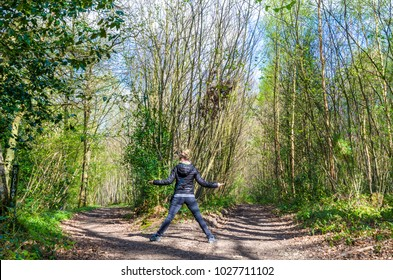 A young hiker woman between two paths diverging in the woods