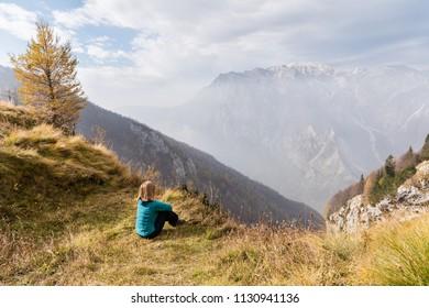 Young hiker woman enjoying mountains view in Alps Europe