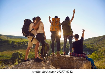 Young hikers with backpacks stand with their backs to the camera and raise their hands while standing on top of the mountain and enjoying nature. Concept of victory and goal achievement.