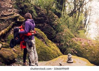 Young hikers couple take rest in mountain  forest. Trekking in Himalayas mountains, Nepal