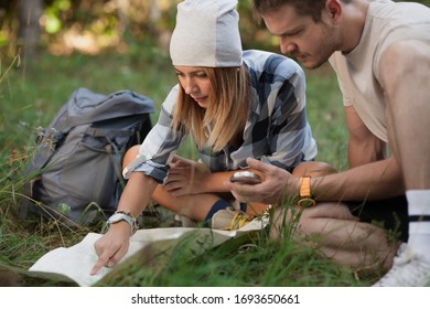 Young hikers sitting on the ground looking at an old map with a compass. Hiking couple in nature.