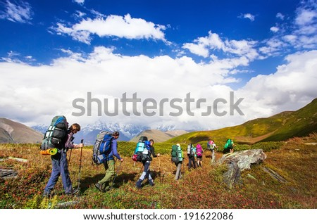 Young hikers trekking in Svaneti, Georgia. Shkhara mountain in the background. Amazingly beautiful WORLD. Fantastic sky background with blue clouds.