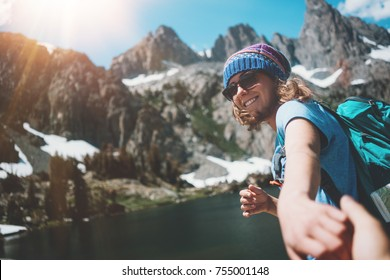 Young hiking couple with backpacks traveling, woman guiding and guy following by the hand into mountain wilderness