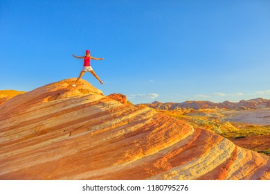Young hiking girl jumping at Valley of Fire on top of Fire Wave at sunset. Happy hiker enjoying view of popular striped lines around the lip of Fire Wave. Nevada, summer travel holidays, United States