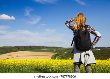 Young hiking woman is looking out over the countryside. Beautiful yellow rape field and blue sky in the background.