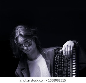 Young Hip hop musician portrait in studio light with a beat machine. Black background,