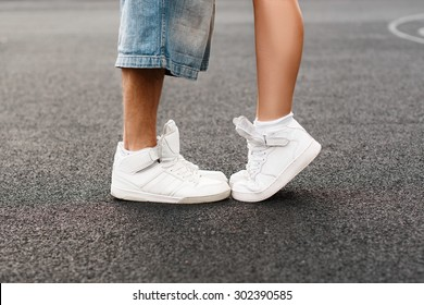 Young hip-hop couple kissing on the background of the asphalt. Kiss love standing. Running white shoes closeup