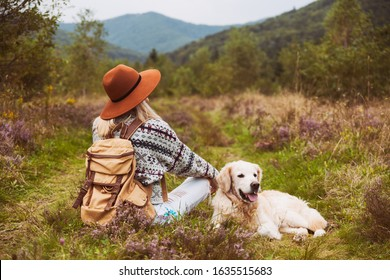 Young hippie blond hair woman in wool sweater with textile backpack and smiling happy golden retriever dog sitting on grass in summer mountains valley. Pets hiking and weekend activities concept.