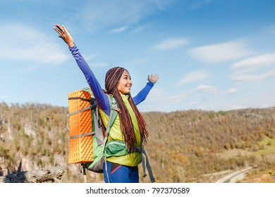 Young hippie girl with afro dreadlocks with backpack hiking in the wild, adventure and youth travel concept