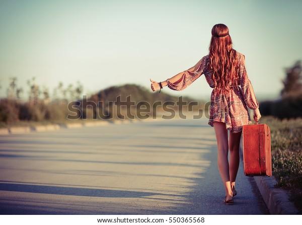 Junge Hippie-Frau, die auf der Straße anschlägt. Rückansicht