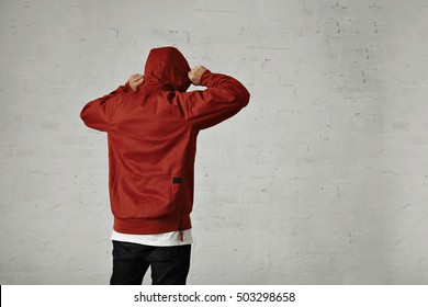 A young hipster adjusts the hood of his brownish red parka, back view, shot in studio with white walls