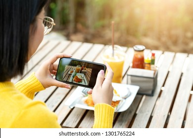 Young hipster asian blogger take photo of food, plate, healthy recipe, lunch meal, breakfast share to story in social media at restaurant or home. Screen showing on moblie phone with blogger concept.