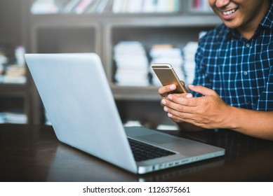 Young hipster asian businessman using smartphone and laptop for Working, Planning projects, Shopping online, Startup business, e-learning, lifestyle, education, concept with copy space.