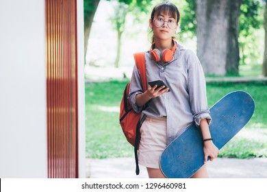Young hipster asian girl holding skateboard.