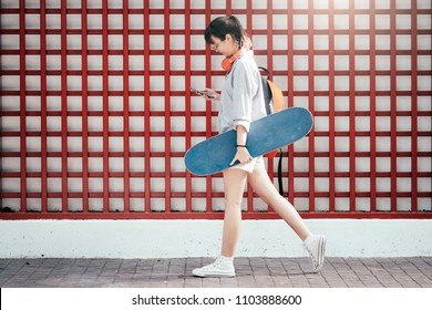 Young hipster asian girl walking and holding skateboard and using mobile phone to chating.