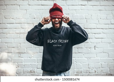 Young hipster in black sweatshirt and red hat with print. Black Friday. Discount, sale, season sales.
