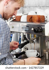 Young hipster blond barista dressed in checkered white blue shirt with trendy barbershop haircut using brewing machinery pouring and preparing fresh cappuccino in big classic white ceramic cup. Cozy