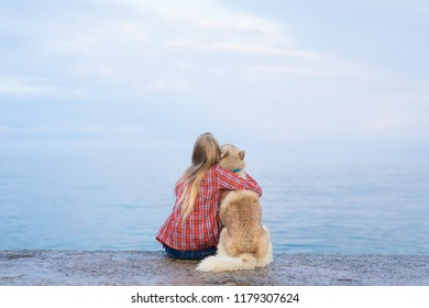 Young  hipster blond  female sitting with siberian husky dog on the sea.  the girl is dressed in a shirt in a cage.