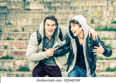 Young hipster brothers having fun with each other - Best friends sharing free time together in urban area outdoors - Handsome guys with winter fashion hoodie clothes enjoying everyday life moments