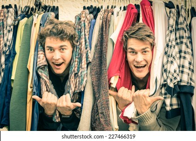 Young hipster brothers at weekly cloth flea market - Best friends sharing free time having fun and shopping in old town on sunny day - Guys enjoying everyday life moments - Retro vintage filtered look