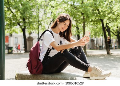 Young hipster brunette girl making a selfie or video with front camera on mobile phone, student having a funny video call and laughing in the park during break in university, wifi in public places