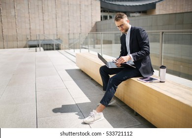 Young hipster businessman in suit typing laptop with coffee near office outdoor