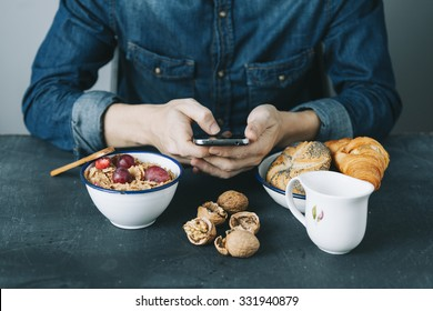 young hipster checking his mobile phone while having a breakfast