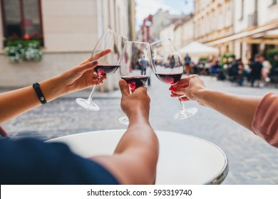 young hipster company of friends sitting in city street cafe, close up hands holding glasses, toasting, celebrating, drinking wine, summer vacation, party, having fun, details