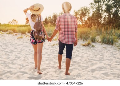 Young hipster couple in love enjoying romantic evening on the beach, holding hands  and watching the sunset.