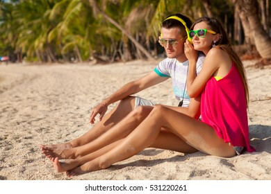 young hipster couple in love, tropical beach, vacation, summer trendy style, sunglasses, headphones