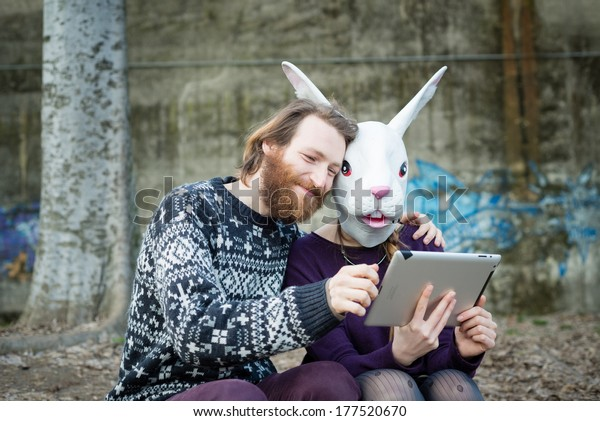 young hipster couple mask rabbit unreal using tablet at the park