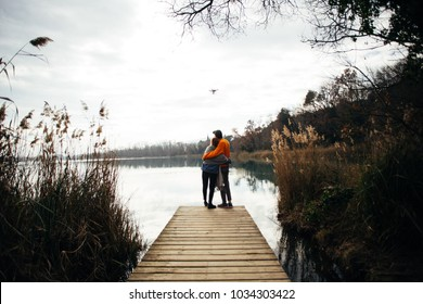 Young hipster couple of millennial teenagers, boyfriend and girlfriend stand on pier or boardwalk in park or forest, watch sunset over lake or river cuddle and hug in relationship goals manner